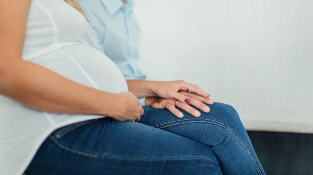Eine schwangere Frau sitzt mit ihrem Partner im Arztzimmer.