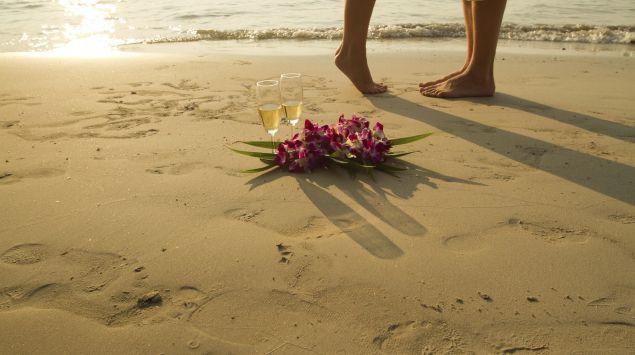 Das Bild zeigt ein Pärchen am Strand mit Sekt und Blumen.