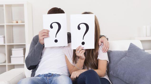 Ein junges Paar sitzt auf einem Sofa und hält sich Fragezeichen vors Gesicht.
