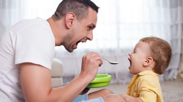 Ein junger Vater füttert seinem Baby spielerisch Brei.
