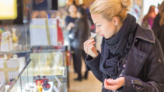 Eine Frau riecht an einer Parfumprobe