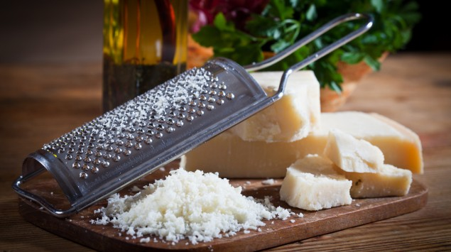 Auf einem Holzbrett liegen ein paar Stücke Parmesankäse, ein Häufchen geriebener Parmesan und eine Käsereibe.