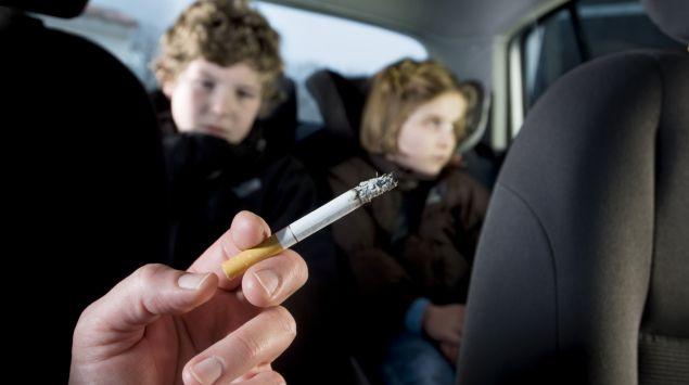 Zwei auf dem Rücksitz eines Autos sitzende Kinder sind dem Zigarettenqualm des rauchenden Beifahrers ausgesetzt.