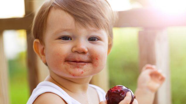 Ein fröhliches Kleinkind isst eine Pflaume.