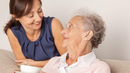 Eine junge Frau kümmert sich um eine ältere Dame.