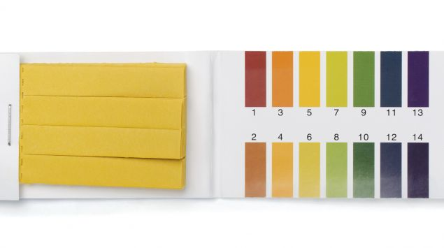 Man sieht ein Heft mit pH-Teststreifen und einer pH-Skala.