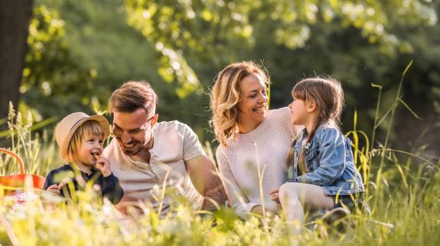 Eine Familie sitzt auf einer Wiese und picknickt.