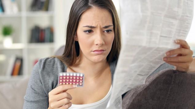 Eine Frau hält einen Pillenblister in der Hand und blickt besorgt auf den Beipackzettel.