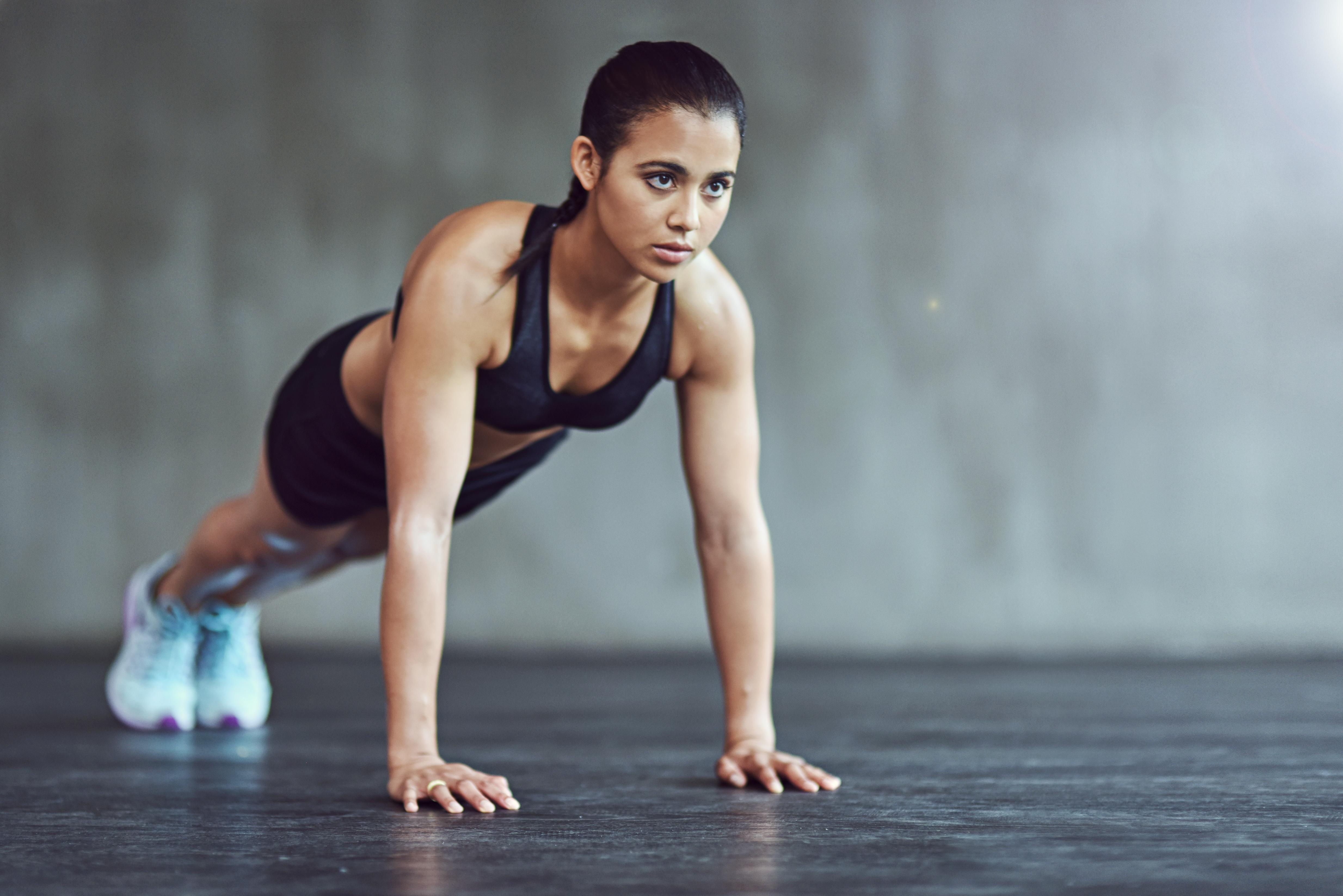 Eine Frau im Sportoutfit macht eine Fitnessübung.