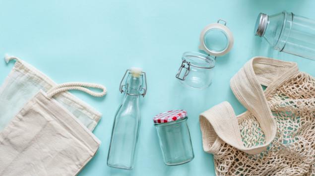 Zu sehen sind verschiedene wiederverwertbare Taschen, Beutel und Glasbehältnisse auf blauem Hintergrund.
