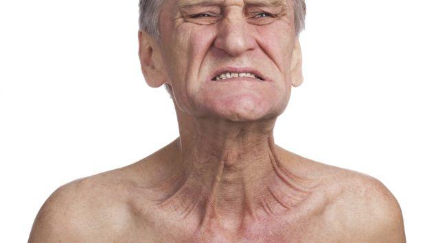 Ein älterer Mann guckt grimmig und spannt sein Platysma an