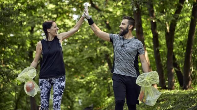 Man sieht einen Mann und eine Frau beim Plogging im Wald.