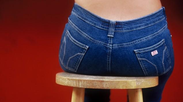 Eine in Jeans gekleidete Person sitzt auf einem Hocker.