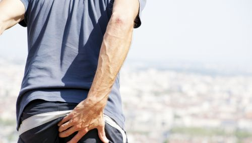 Das Bild zeigt einen Mann, der sich vor Schmerz das Gesäß hält.