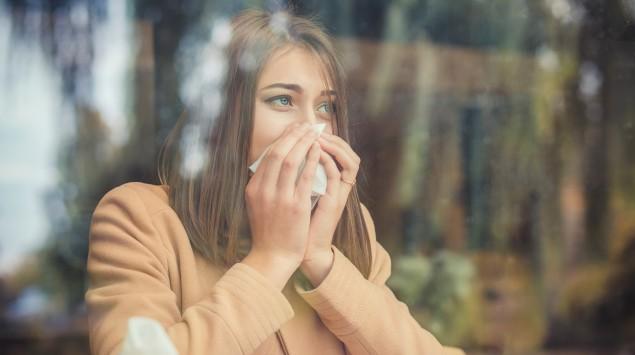 Frau mit Heuschnupfen sitzt am Fenster