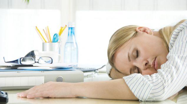 Eine Frau hält ein Nickerchen am Schreibtisch.