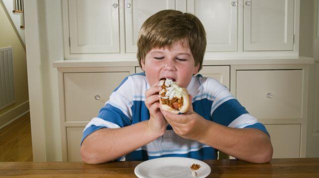Das Bild zeigt einen übergewichtigen Jungen, der einen Hotdog ist.