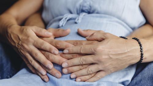 Eine hochschwangere Frau und eine hinter ihr sitzende Person umfassen den Bauch der Schwangeren.
