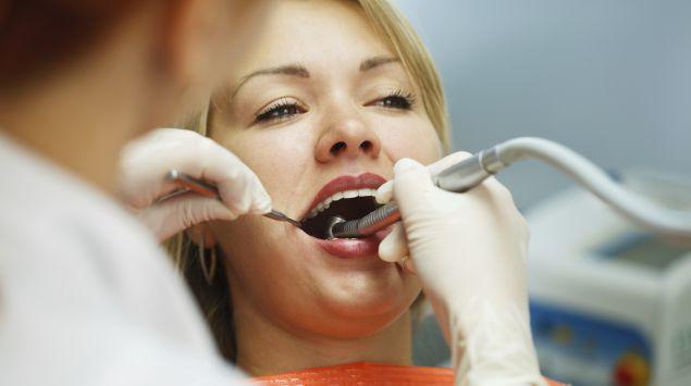 Man sieht eine Frau bei der professionellen Zahnreinigung.