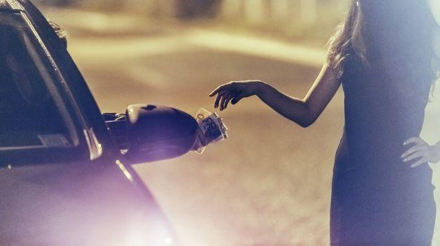 Im Dunkeln steht eine junge Frau neben einem Auto auf der Straße und nimmt vom Fahrer ein paar Geldscheine entgegen.