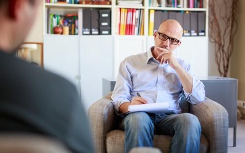 Psychotherapeut sitzt seinem Patienten gegenüber