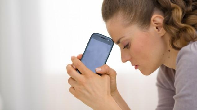 Eine Frau hält ratlos ihr Handy in den Händen.
