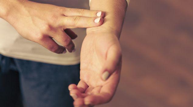 Eine Frau misst ihren Puls am Handgelenk.