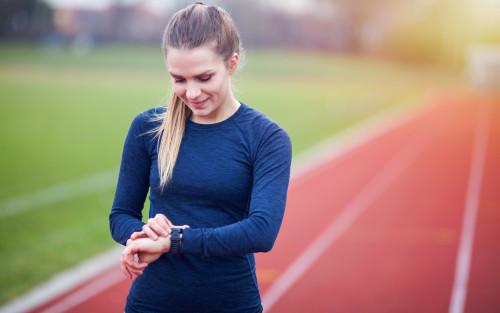 Eine Läuferin schaut auf ihre Pulsuhr.