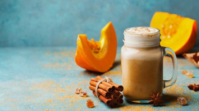Ein Glas mit Pumpkin Spice Latte, Zimtstangen und Kürbissen im Hintergrund.