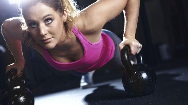 Das Bild zeigt eine Frau, die Liegestütz auf zwei Kettlebells macht.