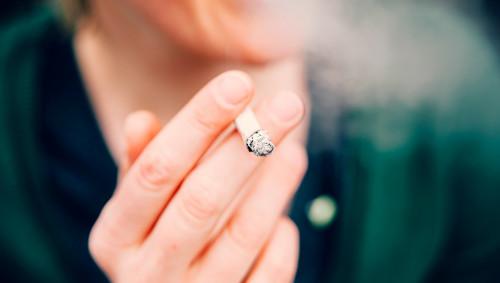 Eine Person hält ein equalmende Zigarette zwischend en Fingern.