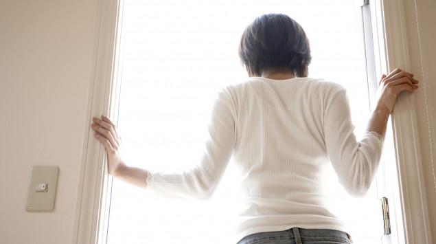 Eine Frau ist wegen des Coronavirus in Quarantäne. Sie schaut aus dem Fenster