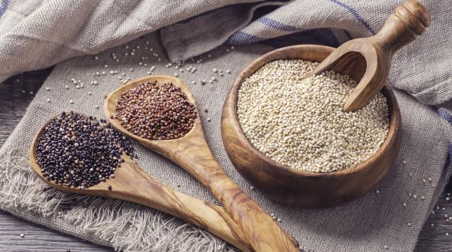 Auf einem Tisch steht eine Hoözschale mit weißem Quinoa, daneben liegen zwei Holzlöffel mit rotem und schwarzem Quinoa.