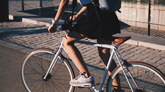 Eine Frau fährt auf einem Rennrad durch die Stadt.