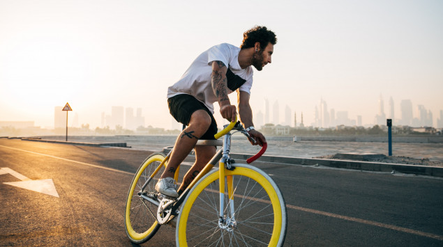 Ein Mann fährt auf einem gelben Fahrrad.