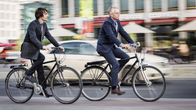 Das Bild zeigt zwei Männer im Anzug, die mit dem Rad durch die Stadt fahren.