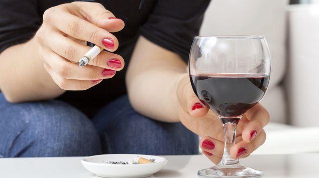 Eine Frau mit einer Zigarette in der Hand, auf dem Tisch daneben ein Glas Rotwein.