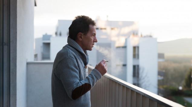 Ein älterer Mann raucht auf dem Balkon.