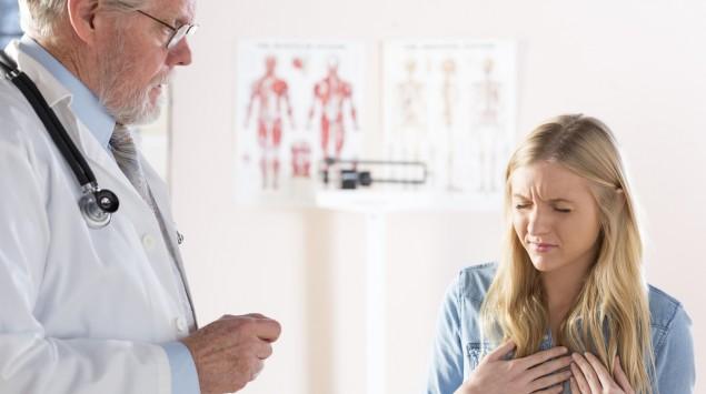 Eine Frau mit Schmerzen im Brust-/Speiseröhrenbereich beim Arzt.