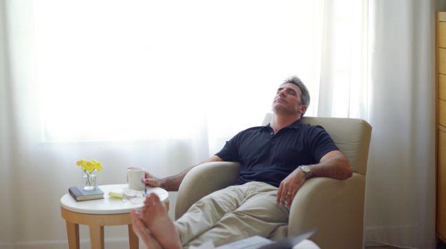 Man sieht einen Mann der mit einem Kaffee im Sessel sitzt und entspannt.
