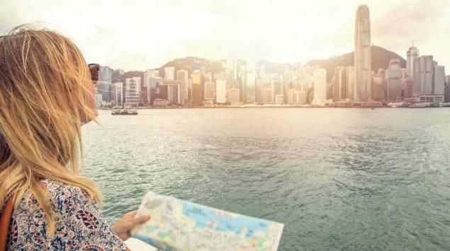 Eine Frau hält einen Stadtplan in der Hand und blickt auf die Skyline von Hongkong.