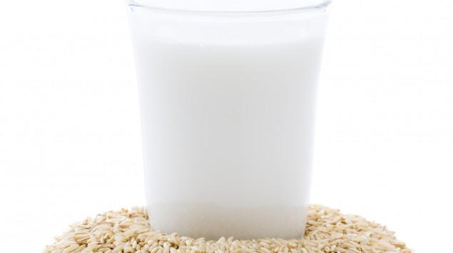 Auf einem Haufen Reis steht ein Glas Milch.