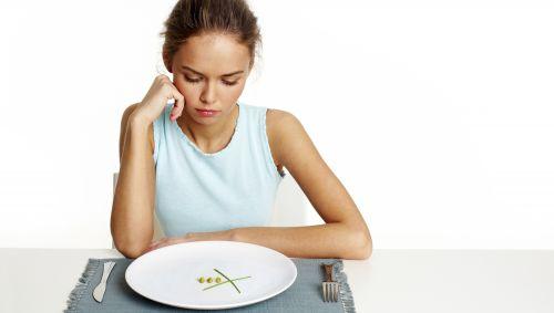 Das Bild zeigt eine Frau, die von einem fast leeren Teller sitzt.