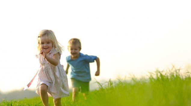 Das Bild zeigt zwei Kinder, die auf einer Wiese Fangen spielen.