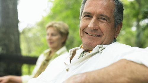 Man sieht einen älteren Mann und eine ältere Frau auf einer Parkbank sitzen.