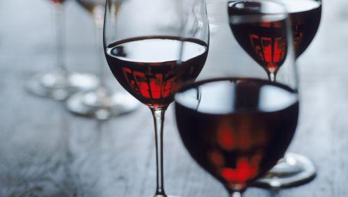 Das Bild zeigt Gläser, die mit Rotwein zur Hälfte gefüllt sind.