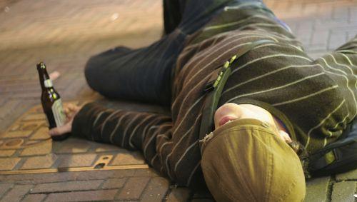 Das Bild zeigt einen besoffenen Jugendlichen, der auf der Straße liegt.