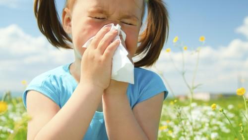 Ein Mädchen sitzt auf einer Wiese und putzt sich die Nase.