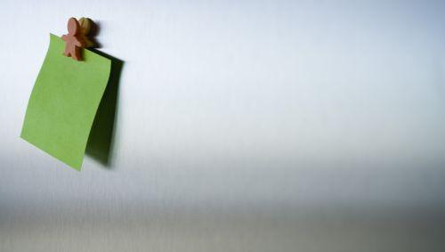 Ein leerer Notizzettel hängt an einer Wand.