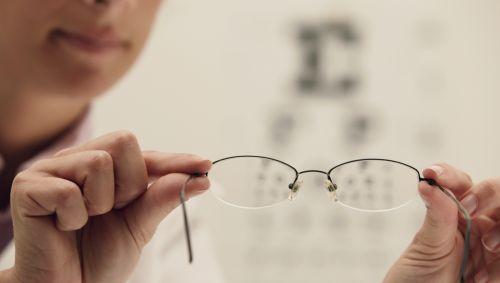 Das Bild zeigt eine Augenärztin, die eine Brille in die Kamera hält.